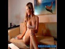 Loira de pernas cruzadas em cima do sofá assistindo filme porno